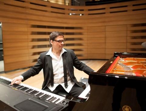 Ron Davis, cravat dénouée et chemise ouverte, joue du piano à queue de la main gauche et du clavier électronique de la main droite.