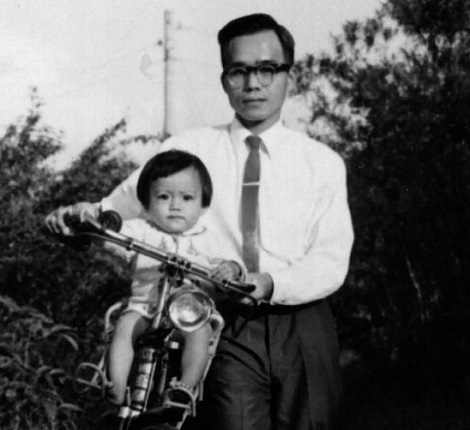 Ruey Yu walks a bicycle, with his toddler daughter sitting on the frame.