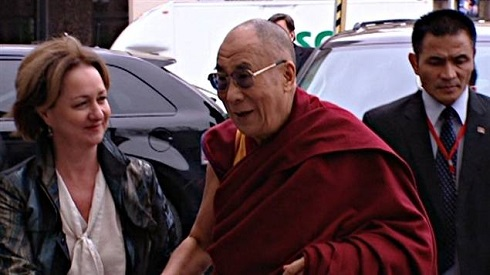 Elizabeth Rody stands next to the Dalai Lama with a car in the background.