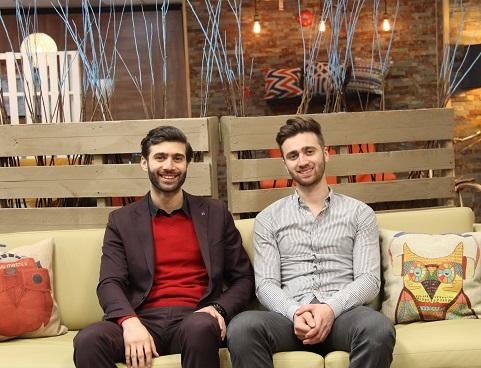 Jamil et Elie Nassif, souriants, assis sur un sofa dans leur magasin de meubles.