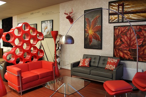 Leather sofas and a glass table with paintings of big leaves on the background wall inside the Zuffa Home furniture showroom.