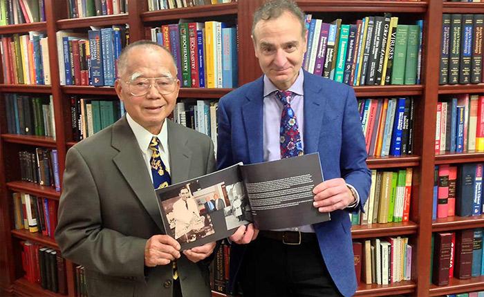 Debout devant une bibliothèque, deux hommes en costume-cravate tiennent ouvert un livre avec des photos anciennes.