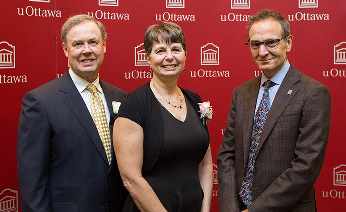 Standing against a red uOttawa backdrop are, from left to right, a man in dark suit with a gold tie, a woman in a black dress and a man in a brown suit wearing glasses