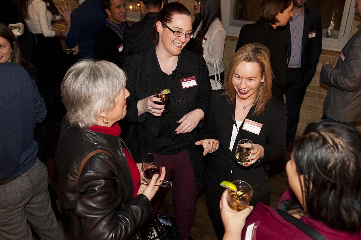 Trois diplômées sont souriant et parlant dans un groupe à un cocktail.