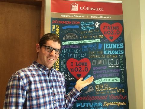 Phil Spencer devant une affiche d'uO2.0 illustrant un cœur et les mots I Love uO2.0 (J'aime uO2.0) et mentionnant d'autres événements.