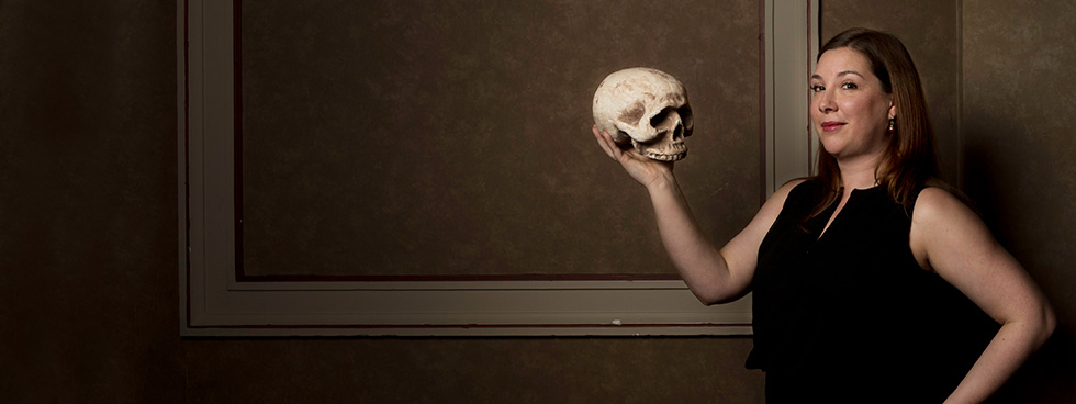 Kathryn Prince holds up a human skull, in the Shakespearean tradition.