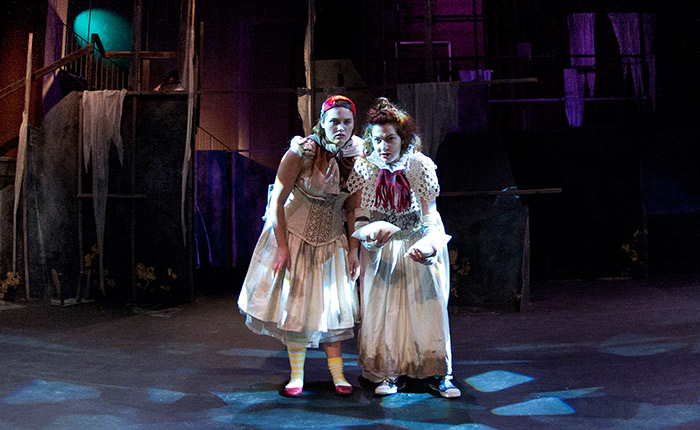 Two women on stage dressed as queens in rags with a staircase in the background.