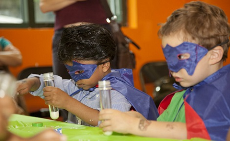 Two young boys, wearing masks and costumes, sit side by side doing an activity at a children's party