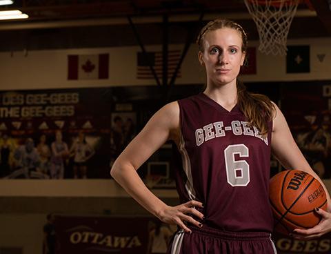 Krista Van Slingerland stands in a gym holding a basketball.