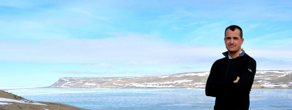 Man stands with arms folded on a stony beach in front of a bay with snowy hills in the distance.