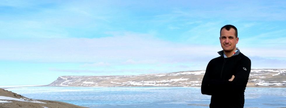 Un homme se tient debout, bras croisés, sur les berges rocheuses d'une baie. Des collines enneigées sont visibles en arrière-plan.