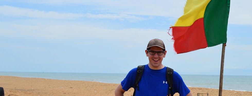 Phil Spencer stands on a beach beside a fluttering Benin flag.