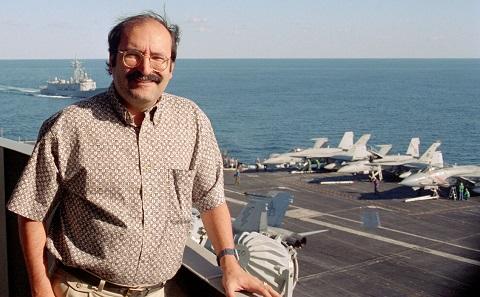 Steven Stein à bord d'un porte-avions, avec des avions de chasse et l'océan en arrière-plan.