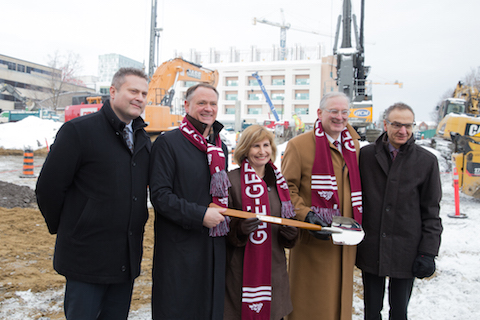 Four men and a woman in winter coats stand, smiling, in front of construction equipment, holding a ceremonial shovel.