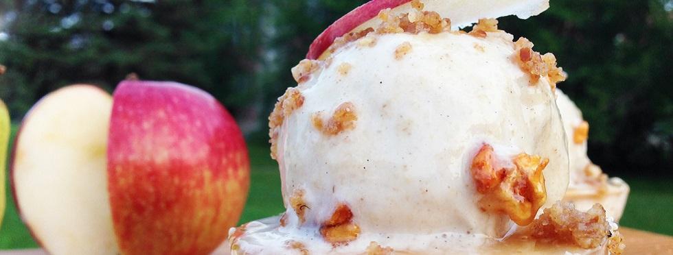 Gros plan sur un dessert glacé assorti de noix de Grenoble et de quartiers de pomme, sur une table en plein air.
