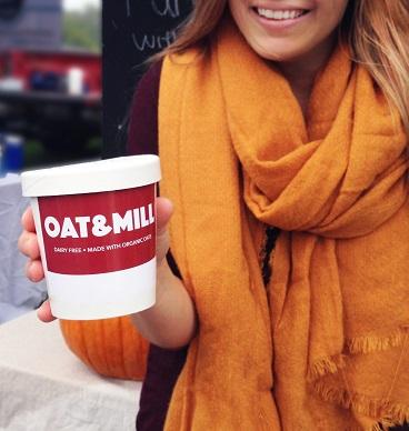 Candace Tierney sourit en tenant une contenant en carton rempli de son dessert glacé, marqué des mots « Oat & Mill », suivis des mots anglais pour « sans produit laitier » et « fait avec de l'avoine biologique »