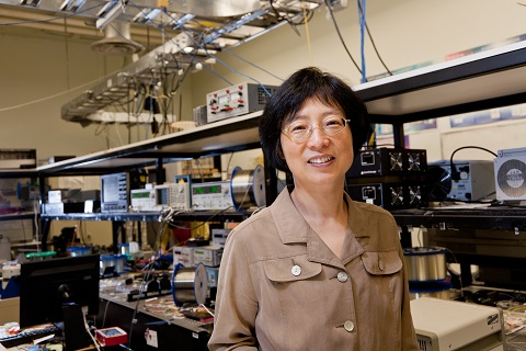 La professeur Xiaoyi Bao de la Faculté des sciences devant de l'équipement de laboratoire.