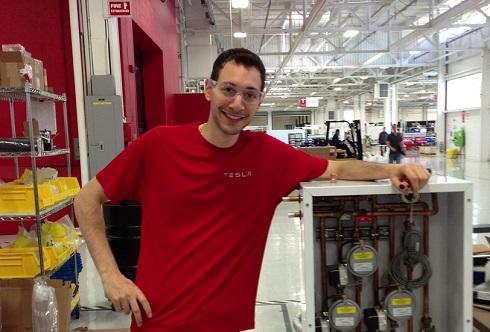 Anthony Bagnulo, les bras autour d'une boîte de tuyaux et de jauges, à l'usine de Tesla Motors.