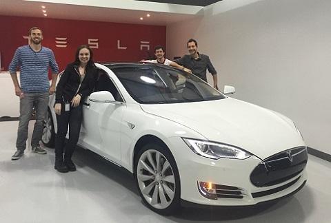 Lucas West, Kirsten Campbell, Geoffrey Maines et Anthony Bagnulo devant une voiture électrique Model S de Tesla.