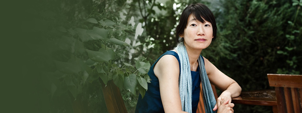 Madeleine Thien sits on a wooden chair in a leafy setting