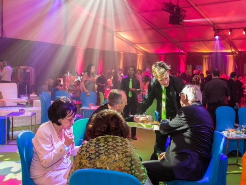 Alumni sit at a table eating and talking as other guests network and mingle under beams of colourful light
