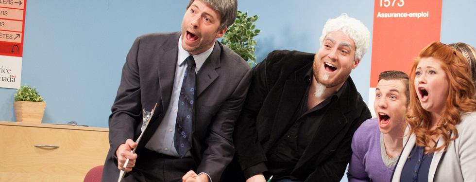 Katherine Levac est sur scène, assise sur une chaise, entourée de quatre autres comédiens. Ensemble, ils crient et rient et ont la bouche ouverte.