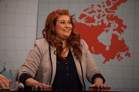 Katherine Levac est assise derrière un bureau avec la carte du monde comme arrière-plan.