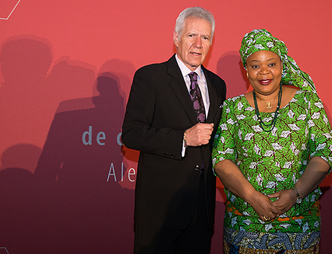 Alex Trebek and Leymah Gbowee stand together on stage.