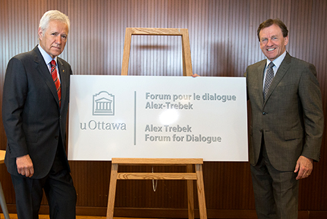 "Alex Trebek and Allan Rock stand on either side of a sign reading ""Alex Trebek Forum for Dialogue""."