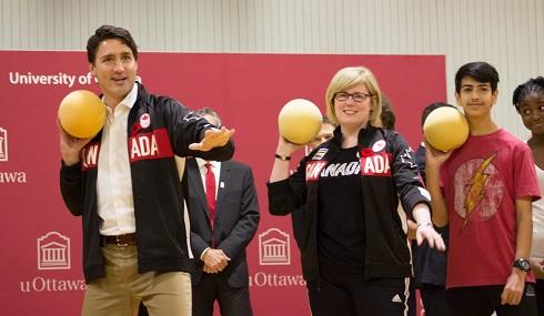 Justin Trudeau, Carla Qualtrough et un élève du secondaire tiennent des ballons comme s'ils s'apprêtaient à les lancer.