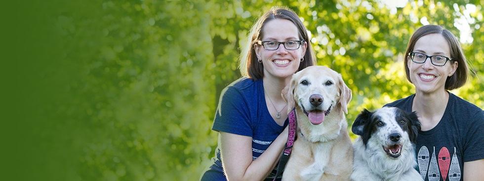 Deux sœurs, souriantes, les cheveux mi-longs et portant des lunettes, sont assises en plein air avec deux chiens entre elles.