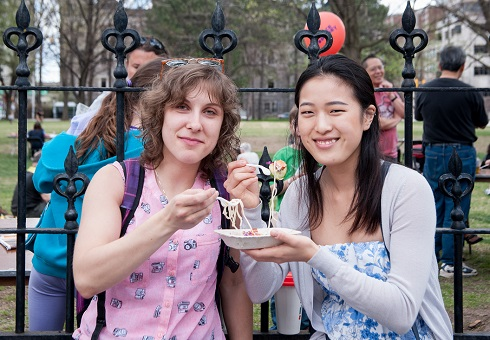 Two young women share some noodles from the same dish while sitting in front of the Tabaret lawn fence.