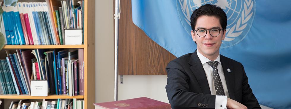 Elias León assis dans son bureau devant le drapeau des Nations Unies.