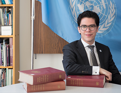 Elias León sits in his office in front of the United Nations flag.