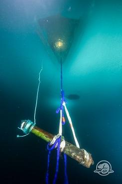 Un canon est suspendu par une corde au-dessous d'un trou triangulaire taillé dans la glace.