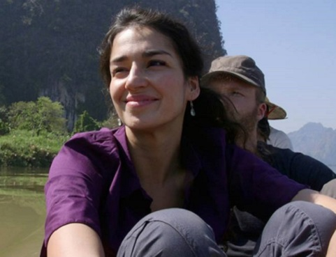 A smiling Nisha on a boat with mountains in the background.