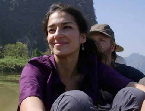 Nisha, sourire aux lèvres, est assise dans une embarcation, sur fond de collines et de ciel bleu.