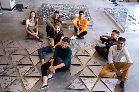 Seven students sit on the floor surrounded by triangular pieces of art.