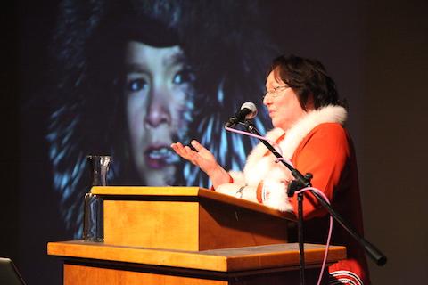 Vêtue d'une veste inuite bordée de fourrure, Sheila Watt-Cloutier se tient derrière un lutrin, d'où elle parle en faisant des gestes. Une photo de son petit-fils dans un parka bordé de fourrure est projetée sur un écran derrière elle