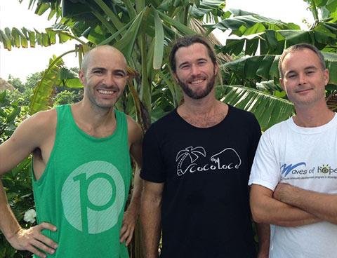 Trois hommes debout devant des palmiers sourient au photographe.