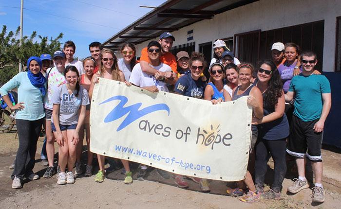 "Une vingtaine de jeunes adultes souriants tiennent une bannière portant l'inscription « Waves of Hope ». | About 20 smiling young adults pose with a banner that reads ""Waves of Hope."""