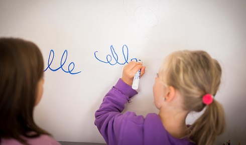 A girl writes on a whiteboard as another girl looks on.