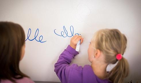 Une fille écrit sur un tableau blanc pendant qu'une autre fille la regarde.