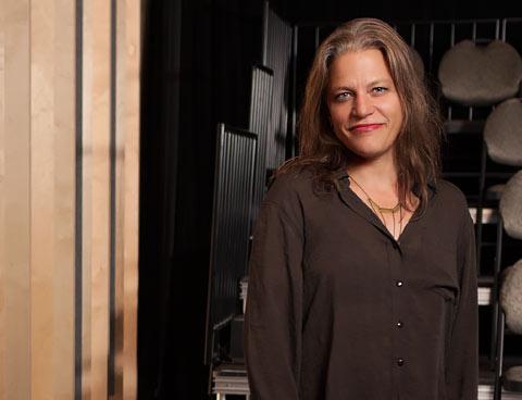 Anne-Marie White debout dans une salle de spectacle devant des sièges à l'arrière-plan.