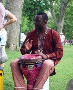 Willy Wandji sits in a park drumming on a djembe