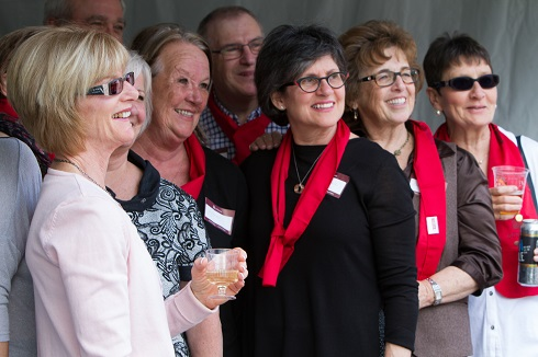 A smiling group of mostly women with two men, several wearing red scarves and paper nametags, looking in the same direction.