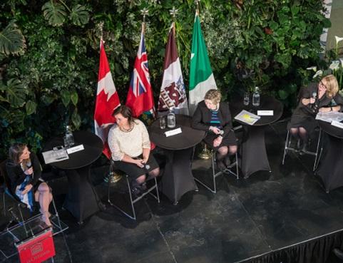 Quatre panélistes sur scène tenant des microphones, devant une rangée de drapeaux.