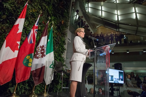 Ontario Premier Kathleen Wynne standing at a podium with flags in the background.