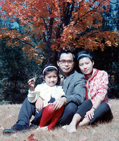 Ruey Yu sits with his wife and daughter on the grass in a park, with fall foliage behind them.