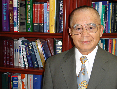 Ruey Yu stands in front of a bookcase containing science-related books.